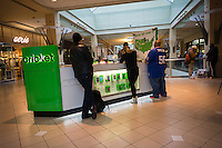 Shoppers at the Cricket mobile phone kiosk in the Queens Center mall in the borough of Queens in New York on Super Saturday, December 20, 2014 looking for bargains for their Christmas gifts. Super Saturday, the Saturday prior to Christmas was crowded with shoppers and is expected to generate more sales than Black Friday.  (© Richard B. Levine)
