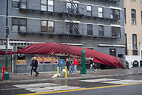 An awning damaged by Hurricane Sandy seen in Chelsea on Tuesday, October 30, 2012. Hurricane Sandy roared into New York disrupting the transit system and causing widespread power outages. Con Edison is estimating it will take four days to get electricity back to Lower Manhattan. (© Frances M. Roberts)