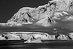 An iceberg floats in front of snow covered mountains, Antarctica