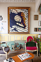 A painting by Yvan Toulouse hangs on the wall of the living room with watercolours by Stephanie de Beauvais placed around the floor