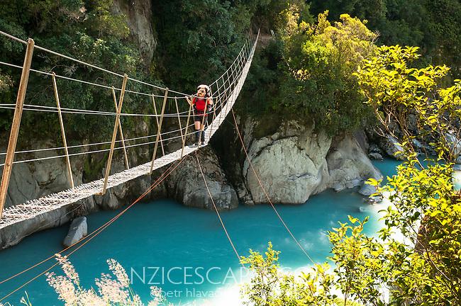 Female tramper crossing a swingbridge over Whataroa River Gorge - South Westland, West Coast, New Zealand MR