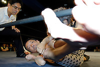 """""""E.T."""" is on the ropes as referee Shinsuke Funabashi watches ."""