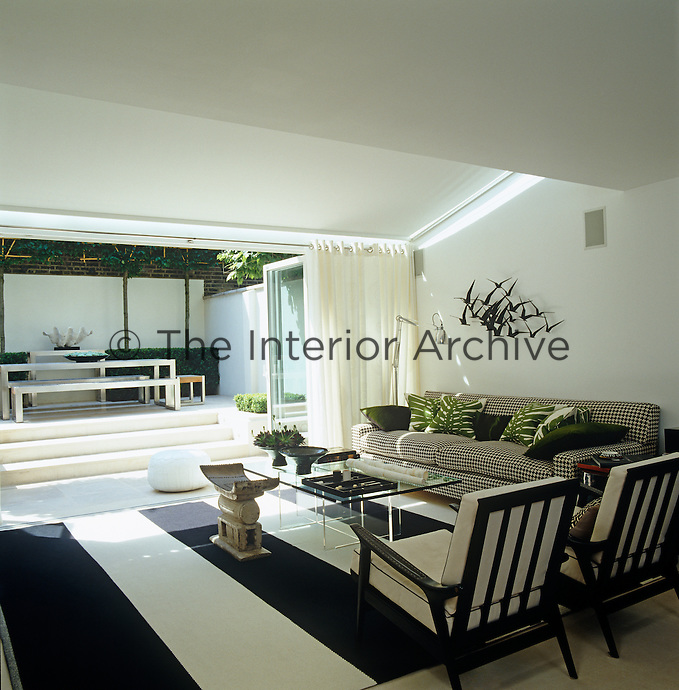The family room with its boldly striped black and white rug opens into the courtyard garden