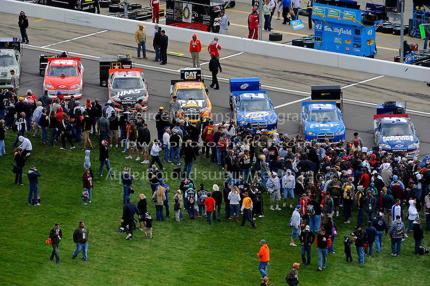 Fans view cars gridded along pit lane.