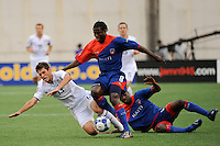 Colin Clark (13) of the United States (USA) goes down in a collision with a pair of Haitian players. The United States and Haiti played to a 2-2 tie during a CONCACAF Gold Cup Group B group stage match at Gillette Stadium in Foxborough, MA, on July 11, 2009. .