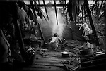 Women cooks in her kitchen completely exposed by the slicing winds of Cyclone Nargis, Irrawaddy River Delta, Kyaiklat, Burma (Myanmar).