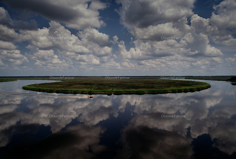 A lone motorboat cuts through reflections of clouds in placid waters of the St. Marys River in Southern Georgia. The St. Marys divides Florida and Georgia as it flows east to the Atlantic Ocean from the Okefenokee Swamp.