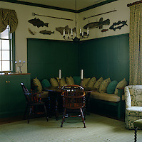 An L-shaped wooden banquette has been painted green to match the cupboards in the dining area of this country living room