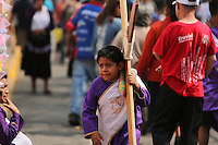 Mexico City, Mexico. 18th April 2014 - A boy carries a wooden cross while revellers take part in a performance of the passion of Christ at the Holy Friday celebrations, in Iztapalapa, Mexico City, capital of Mexico. Photo by VIEWpress/Miguel Pantaleón