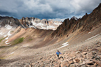 Female hiker ascending the rocky south slopes of Lavender Col route on Mt. Sneffels (14150 ft), San Juan mountains, Colorado, USA