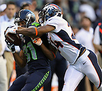 Seattle Seahawks wide receiver Golden Tate catches a 33-yard pass while being defended by is grabbed by Denver Broncos cornerback Champ Bailey at CenturyLink Field in Seattle, Washington on  August 17, 2013. The Seattle Seahawks beat the Broncos 40-10.     ©2013. Jim Bryant Photo. All Rights Reserved.
