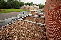 Compost, covered with wood chips, sits in three piles on the grounds of the old Holmesburg Prison. The compost remains in these piles for thirty days, as a ventilation system blows air from the bottom of the piles to keep the compost dry. After thirty days, inmates transfer the compost to another pile to further decompose for another ninety days. The composting program is a pilot program of the Philadelphia Prison System that involves inmates from the Alternative Special Detention Center on State Road.