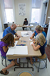 Katherine Cochran-Hill (left) and her dad James Hill along with Ella Kushnick (right) and her mom Shannon Kushnick create their own stamps at the Sunday Family Art Encounters at the Kennedy Museum of Art.