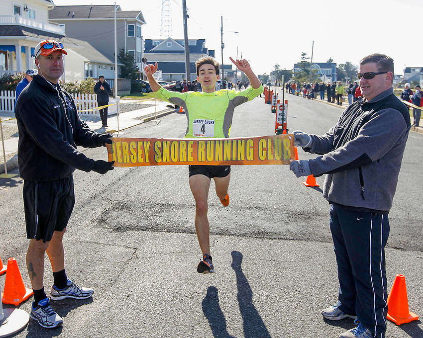 Liam Wall of Manasquan wins first annual Manasquan Turkey Run on Sat., Nov. 22, 2014. Holding the finish line are race director Carmen Triggiano (left) and Manasquan Borough Councilman Owen McCarthy. (Andrew Mills Digital Media)