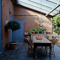 The mellow brick walls of the farmhouse create the perfect outside dining room with a covered canopy
