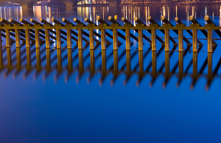 Logs and columns reflected in Vltava river in Prague at night.