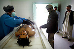 Imam Gul, right, 25, stands next to the body of Hamidullah, 22, while the body is prepared for burial at the Mirwais Hospital morgue in Kandahar, Afghanistan, April 23, 2009. The day before, Ahmad Shei, 25, and Hamidullah, 22, were in an unarmored truck carrying material to a checkpoint in Zabul Province when their vehicle was hit by a roadside bomb. Four other border policemen were injured and taken to Kandahar Air Field to receive medical treatment. The two dead were to the morgue at Mirwais Hosptal before being transported to their home provinces in the North for burial. Despite worsening security, development continues at Mirwais Hosptial, where the International Committe of the Red Cross conducts training and assists the local staff. Mirwais is the main public hosptial serving five southern provinces. As security has deteriorated in the South, many international NGO's have pulled their staff from the area or shut down the regional office, stunting development in a region where it is badly needed.