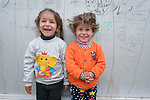 """Displaced children pose outside their familiy's """"caravan,"""" a manufactured housing unit offered to some displaced families in the village of Bakhtme, Iraq. The community was flooded with displaced families when the Islamic State group took over nearby portions of the Nineveh Plains in 2014. The community includes a """"child-friendly space"""" sponsored by the Christian Aid Program Nohadra - Iraq (CAPNI), offering displaced children and children from the host community an opportunity to play and learn."""