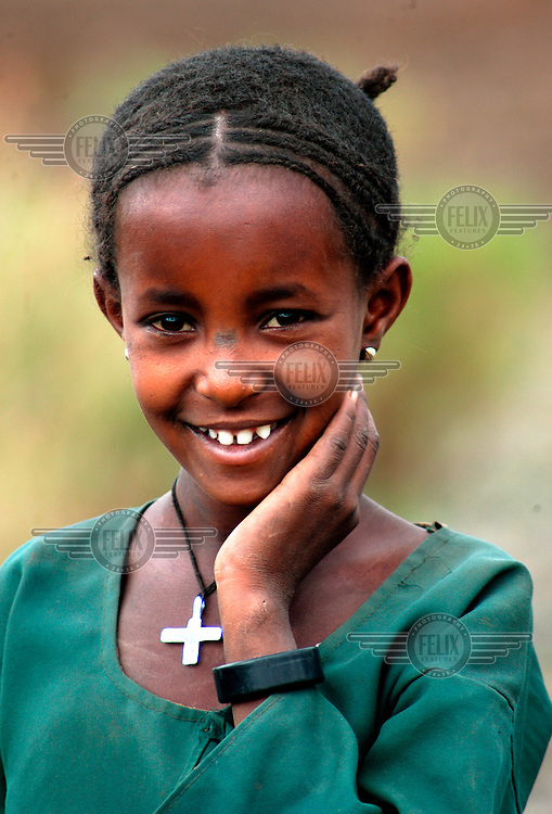 A young schoolgirl wearing a crucifix necklace is pictured smiling outside her school on the last day of term.