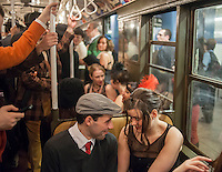 New Yorkers, tourists and subway buffs, some in period garb, travel on a vintage MTA Nostalgia Train Christmas season ride on Sunday, December 16, 2012. The straps, ceiling fans and rattan seats are a far cry from the plastic and air conditioning in modern subway cars. The Metropolitan Transit Authority has several of these trains for the various subway lines which they put into use for special occasions. the trains normally reside in the New York City Transit Museum in downtown Brooklyn where they can be visited every day. (© Richard B. Levine)