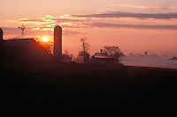 Early morning sunrise mist hovers over bucolic farm landscape.  Lancaster county, PA.