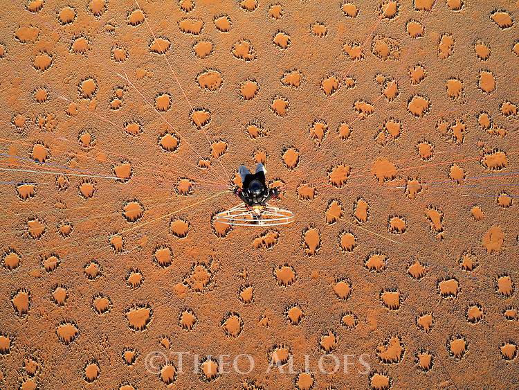 Namibia, Namib Desert, Namibrand Nature Reserve, Theo Allofs flying with a powered paraglider over desert covered with fairy circles
