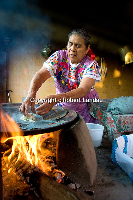 Woman cooking with blue corn tortillas and cheese at workshop in Oaxaca