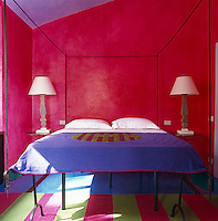 A wrought-iron four-poster bed with walls painted a combination of cerise and purple and with a purple bed cover to match