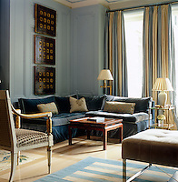 The elegant floor-to-ceiling curtains in the living room of a New York apartment were made from two different colours of silk taffeta joined to form wide stripes and the striped dhurrie is a 19th century antique from Agra