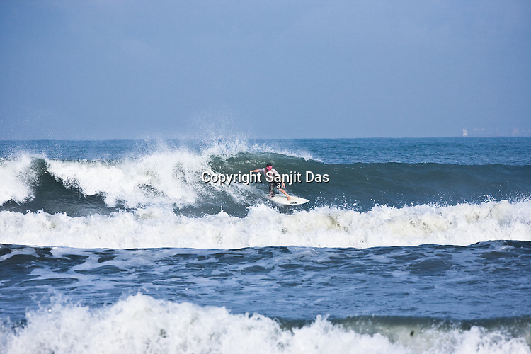 """Jeera Krishna Dasa, one of the Krishna devotees from the Kaliya Mardana Krishna Ashram is seen surfing on the Arabian Sea on the beach front of Mangalore, Karnataka, India.  ..Krishna devotees in the Gaudiya Vaishnava tradition of Hinduism, they are known collectively as the """"surfing swamis."""" The """"surfing ashram"""" is growing in popularity and surfing here is a form of meditation, a spiritual practice leading to heightened states of awareness."""