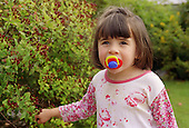 Young girl with autism standing outside in garden sucking on dummy.  MR