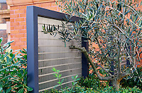 Detail of  steel fence panels  with planted Buxus and olive tree