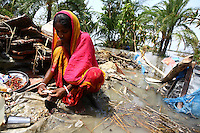A woman prepares food, surrounded by stagnant floodwaters. Thousands of people were displaced in Shyamnagar Upazila, Satkhira district after Cyclone Aila struck Bangladesh on 25/05/2009, triggering tidal surges and floods..