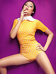 Young woman wearing bright yellow vintage style clothes on purple background. Sensual high fashion photo.