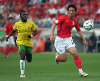 Togo's Kader Mohamed (17) and Korea Republic's Jin Kyu Kim (6) chase the ball. Korea Republic defeated Togo 2-1 in their FIFA World Cup Group G match at the FIFA World Cup Stadium, Frankfurt, Germany, June 13, 2006.