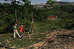 Pedro Ignacio Guzman (in red) oversees the construction of a new home in the eastern end of La Cerca. Despite the community's bleak future, locals refuse to sell their lands. ?This is our land, and we will stay,? states Guzman. Barrick and Goldcorp's Pueblo Viejo open-pit gold mine threatens the cocoa-bean producing community of La Cerca. Cotuí, Sánchez Ramírez, Dominican Republic. April 2012.