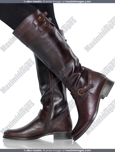 Woman wearing knee-length brown leather fashion boots isolated on white background