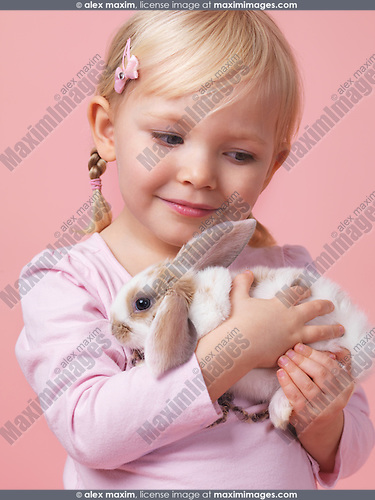 Portrait of a three year old girl holding a pet rabbit isolated on pink background