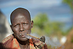 A woman smokes a pipe in a camp for displaced people in Melijo, South Sudan, near that country's border with Uganda. Families here fled fighting around Bor, in Jonglei State, in December 2013, but have not been warmly welcomed to this region of Eastern Equatoria State, where two earlier waves of displaced people in the 1980s and 1990s have left relations tense between the newcomers, who are Dinka, and the largely Ma'adi residents around the city of Nimule. The ACT Alliance is helping the displaced families and the host communities affected by their presence, and is supporting efforts to reconcile the two groups.