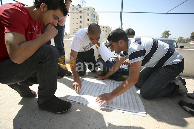 Palestinian general secondary students read a local newspaper to find their results in the West Bank city of Ramallah on July 22, 2010. Photo by Eyad Jadallah