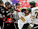26 November 2010: University of Vermont Catamount forward Wahsontiio Stacey (9), a Senior from Kahnawake, Quebec, and Northeastern University Huskie forward Steve Quailer, a Sophomore from Arvada, CO, get into a scuffle during overtime at Gutterson Fieldhouse in Burlington, Vermont. Both players received 5-minute majors for face-masking as the Huskies came back from a 2-0 deficit to earn a 2-2 tie against the Catamounts. Mandatory Credit: Ed Wolfstein Photo