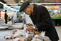 Man choosing shrink wrapped food in supermarket, Chongqing, China