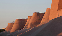 Low angle view of the Wall of the old city, Khiva, Uzbekistan, pictured on July 7, 2010, at sunset. Khiva's old city, Ichan Kala, is surrounded by 2.2 kilometres of crenellated and bastioned city walls. Some sections may be 5th century, but the strongest sections were built 1686-88 by Arang Khan. Khiva, ancient and remote, is the most intact Silk Road city. Ichan Kala, its old town, was the first site in Uzbekistan to become a World Heritage Site(1991). Picture by Manuel Cohen.