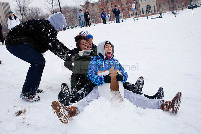 """Sophmores ReDell Atkinson, Julia Vega and Sarah Smith scream while being pushed down the hill on a piece of cardboard in """"the Bowl"""" outside William T. Young Library in Lexington, Ky., on Monday, February 3, 2014. Photo by Emily Wuetcher  