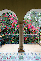 Arches and red flowers, Hotel Hacienda Uxmal near the Mayan ruins of Uxmal, Yucatan, Mexico.