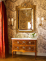 An antique chest of drawers with a marble top stands under an antique mirror in a room decorated with a toile de Jouy wallpaper