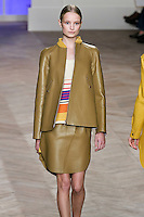 Maud Welzen walks the runway in a mustard leather zip--front baseball jacket, ivory/orange/yellow/blue striped silk tank top with shirttail hem, and mustard leather skirt with shirttail hem, by Tommy Hilfiger for the Tommy Hilfiger Spring 2012 Pop Prep Collection, during Mercedes-Benz Fashion Week Spring 2012.
