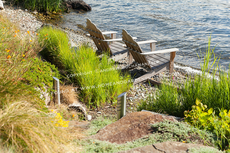With a meadow garden behind, two Adirondack chairs offer a relaxing spot to sit on the shoreline.