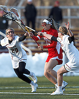 Boston University midfielder Sofia Robins (24) takes a shot as Boston College midfielder Kate McCarthy (20) and Boston College midfielder Sarah Mannelly (6) defend..Boston College (white) defeated Boston University (red), 12-9, on the Newton Campus Lacrosse Field at Boston College, on March 20, 2013.