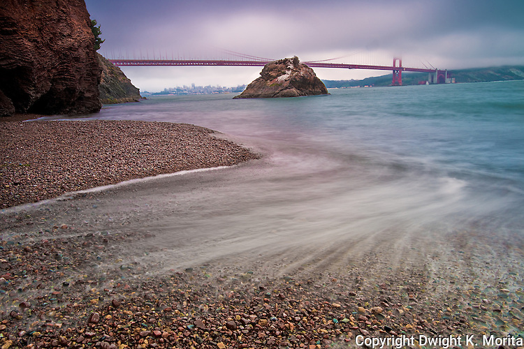 Wave washes over gem colored stones on the beach of Kirby Cove with the Golden Gate Bridge and San Francisco in the background.